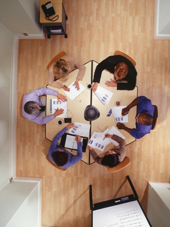 group of people sitting around a meeting table