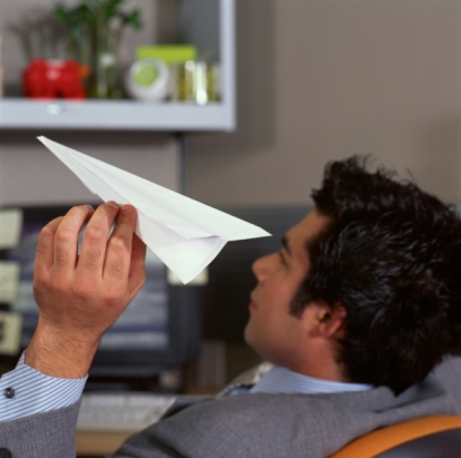 man at desk with paper airplane
