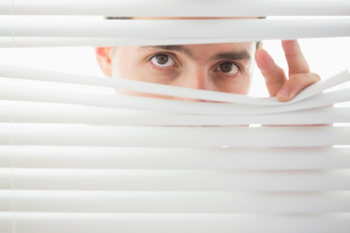 suspicious_male_looking_through_blinds