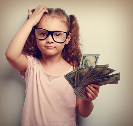 young_girl_in_glasses_scratching_head_holding_handfull_of_money