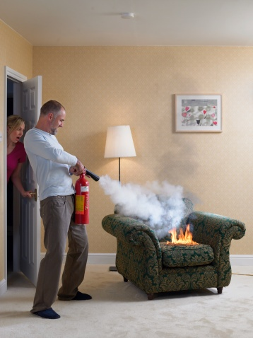 man_extinguishing_fire_on_arm_chair